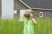 Girl in weeds with old camera — Stock Photo