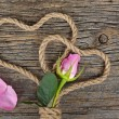 Pink rose bud and rope hearts — Stock Photo #64991901