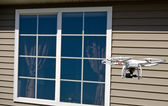 Drone hovering near house window — Stock Photo