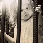 Little girl hanging on to metal railing — Stock Photo #70205715