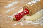 Wooden rolling pin on bread dough — Stock Photo