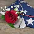 Rose and dog tags on flag — Stock Photo #74581373