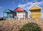 Colorful beach huts on a shingle beach — Stock Photo