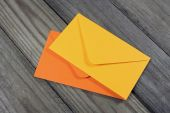 Yellow and orange envelopes on wooden background — Stock Photo