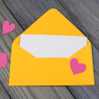 Love letter- yellow envelope with paper heart on blank card on wooden background — Stock Photo #53044667