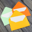 Three colorful open envelopes with blank cards on wooden background — Stock Photo #53068083