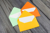 Three colorful open envelopes with blank cards on wooden background — Stock Photo