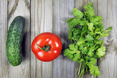 Coriander, tomato and cucumber on wooden surface — Photo