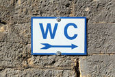 Toilet sign on old stone wall — Stock Photo
