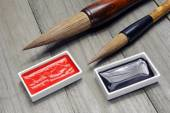 Asian writing brushes and ink for calligraphy on wooden background — Stock Photo