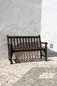Vintage wooden bench against whitewashed wall — Stock Photo