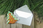 Christmas fir tree, silver envelope with gingerbread on wooden background — ストック写真