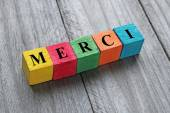 Word merci (thank you in french) on colorful wooden cubes — Stock Photo