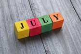 Word july on colorful wooden cubes — Foto Stock