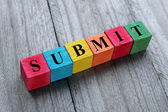 Word submit on colorful wooden cubes — Stock Photo