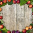 Beautiful frame of small red-ripe apples with green leaves on raw wooden background. — Stock Photo #53800743