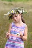 Girl tears off petals of daisy — Stock Photo