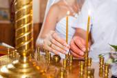 Man and woman put a candle in church — Stock Photo