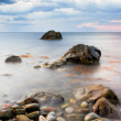 Seascape. Seashore with misty water at sunset — Stock Photo #78093870
