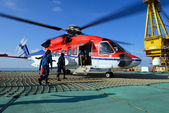 The helicopter landing officer take care passenger to embark hel — Stock Photo