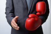 Businessman remove boxing gloves to offer a handshake on white b — Stock Photo