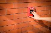 Hand of woman is pulling fire alarm on the brick wall — Stock Photo