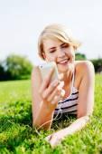 Kvinna på gräs som lyssnar på musik — Stockfoto