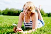 Woman on grass listening to music — Stock Photo
