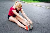 Pareggiatore femminile lo stretching prima di una corsa — Foto Stock