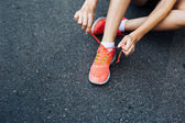 Female runner lacing her shoes — Stock Photo
