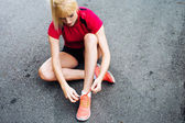 Female runner lacing up her shoes — Stock Photo