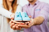 Prengant couple holding baby shoes — Stock Photo