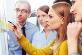 Salespeople looking at board — ストック写真