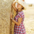 Girl near haystacks in cowboy hat — Stock Photo #58939213