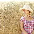 Girl near haystacks in cowboy hat — Stock Photo #58939233