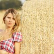 Young girl near haystack — Stock Photo #58939283