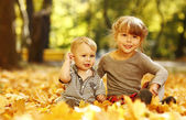 Girl with brother playing in autumn park — Stock Photo