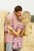 Couple embracing near haystacks — Stock Photo