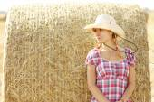 Girl near haystacks in cowboy hat — Stock Photo