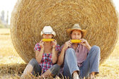 Couple on haystacks in cowboy hats — Stock Photo