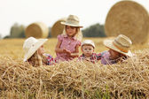 Family on haystacks in cowboy hats — Stock Photo