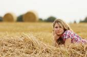 Young girl near haystack — Stock Photo
