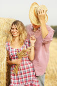 Couple near haystack in cowboy hats — Stock Photo