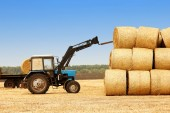 Tractor with yellow haystacks — Stock Photo