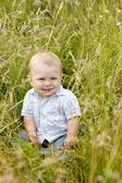 Boy sitting on grass — Stock Photo