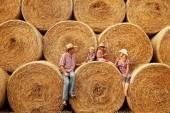 Family sitting on haystacks in cowboy hats — Stock Photo