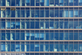 Glimpse into the workplaces of an office building with blue glas — Stock Photo