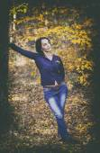 Vintage portrait of beautiful girl in jeans leaning in autumn fo — Стоковое фото