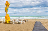 Beach landscape with colored umbrellas, nice sand and blue sky — Stock Photo