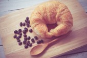 Fresh Croissants on wooden with retro filter effect — Foto Stock